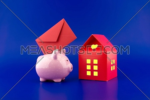 Red envelope being inserted into a cute pink piggy bank next to a small red house of paper with warm light in windows over festive blue background with copy space