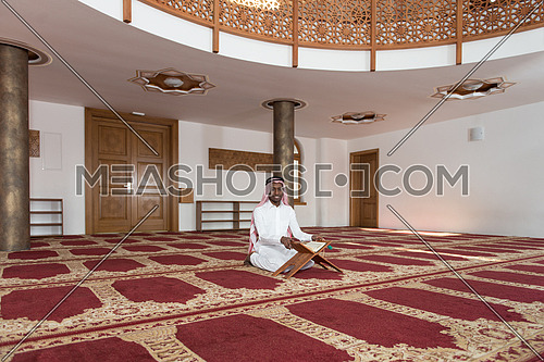 Black African Muslim Man Making Traditional Prayer To God While Wearing A Traditional Cap Dishdasha
