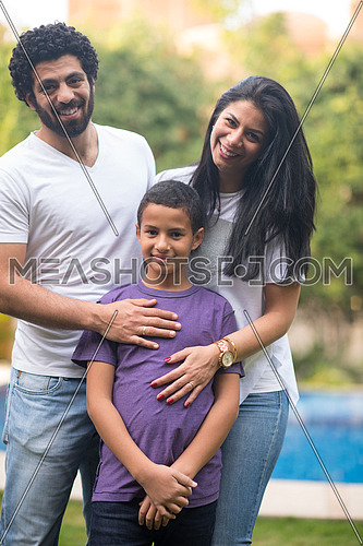 Portrait of a young middle east couple with their son in the yard by the pool