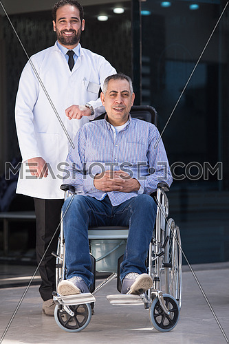 middle eastern sick man in a wheelchair and a young doctor in front of a large modern hospital