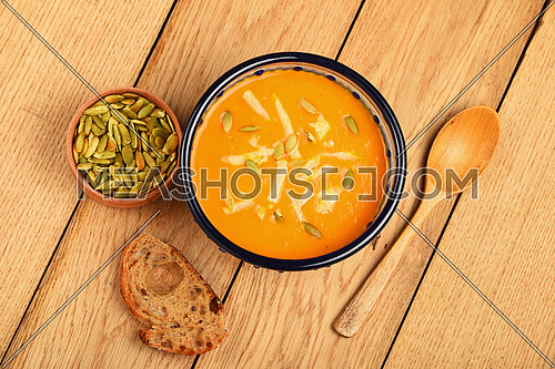 Ceramic bowl of pumpkin cream soup, spoon, slice of bread and seeds on wooden table background, top view
