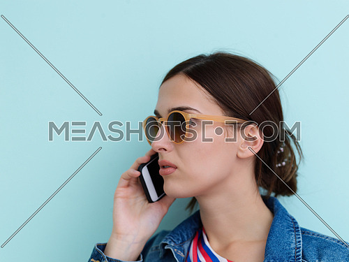 Portrait of young girl talking on the phone while standing in front of blue background. Female model wearing sunglasses representing modern fashion and technology concept