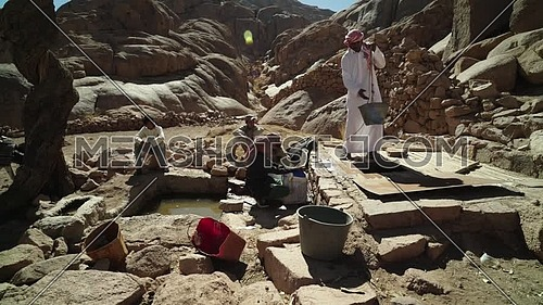 Follow shot for bedouins get water from Ain hudra at Sinai Mountain at day.
