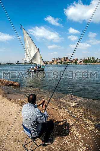 A man sitting on a chair fishing in the river nile
