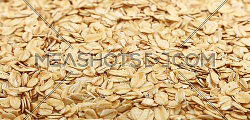 Flakes of porridge oat grits for oatmeal close up pattern background, low angle view, selective focus