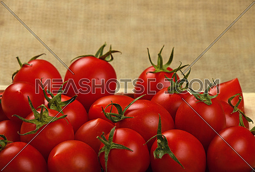 Red ripe fresh cherry tomatoes in small wooden box with on burlap jute canvas background, close up