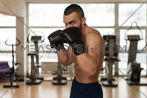 Young Muscular Sports Guy In Gloves With A Naked Torso Boxing