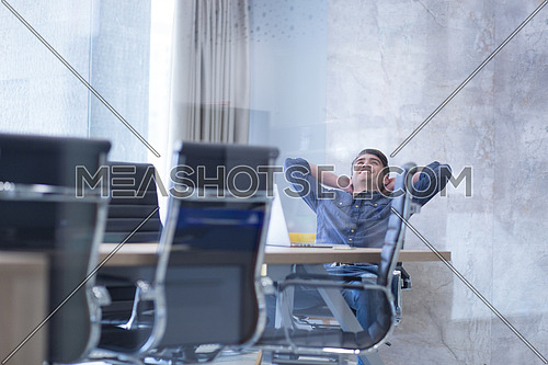 A time for relax. Young tired casual businessman relaxing at the desk in his office