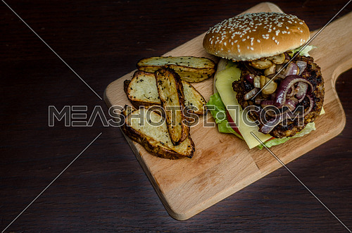 cheese burger sandwich on a brown table and a chopping board