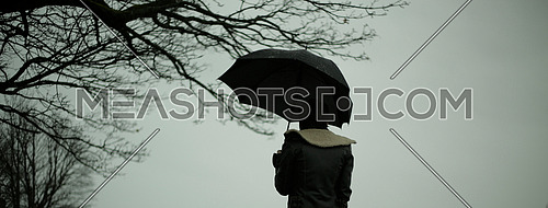 A person holding an umbrella during a rainy day