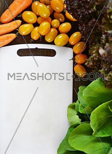Organic garden vegetables ingredients around white cutting board, top view, copy space. Healthy food and diet nutrition concept.