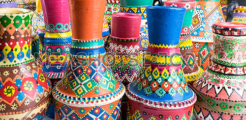 Front view showing a composition of artistic painted colorful decorated handcrafted pottery vases