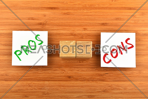 Choice, dilemma, two white paper notes with marker writter pros and cons words, wooden holders in different directions on bamboo wooden background for presentation