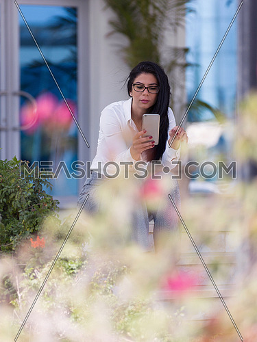 young business woman making phone call and sitting on steps in front of corporate business building