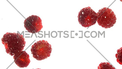 Close up several fresh red ripe raspberries thrown and floating in clear transparent water, low angle side view, slow motion
