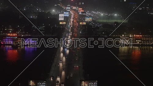 Ariel shot fly over Cairo City at Tahrir Area showing traffic, 6th of October Bridge and The River Nile at night - Novermber 2018