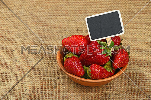 Fresh mellow red strawberries in rustic ceramic bowl with chalk blackboard price tag sign on jute burlap canvas background, high angle view