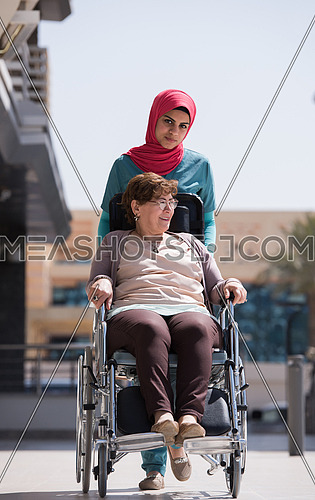 older sick woman in wheelchair with young middle eastern  nurse in front of a large modern hospital