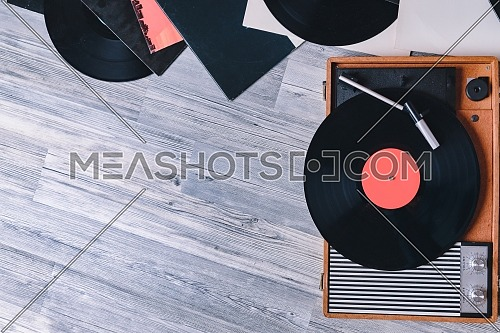 Gramophone vinyl record player on the background of their gray wooden boards. Needle on a vinyl record. Black vinyl record,Sound technology for DJ to mix & play music.