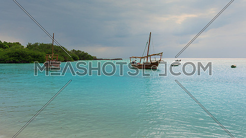 Anchored wooden dhow boats on the amazing turquoise water in the Indian ocean  Zanzibar, Tanzania.