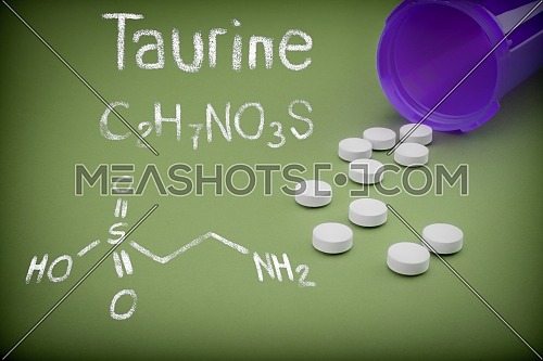 Pills spilling from an open bottle on green background, Chemical formulation of taurine written with chalk, conceptual image
