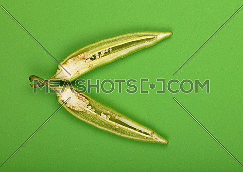 Two cut crossed halves of fresh jalapeno hot chili pepper on green paper background, close up, elevated top view