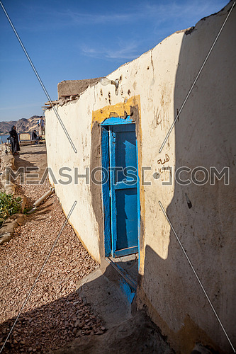 Long shot for a Nubian House with Blue door at day