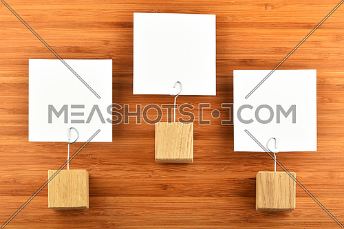 Hierarchy - Three white paper notes with wooden holders isolated bamboo wooden background for presentation