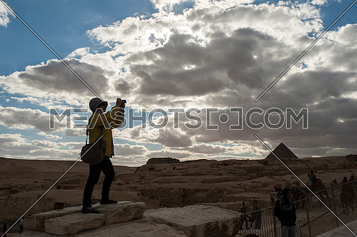 a tourist in silhouette taking picture at the Pyramids of Giza - The greatness of the Egyptian civilization أهرامات الجيزة عظمة الحضارة المصرية