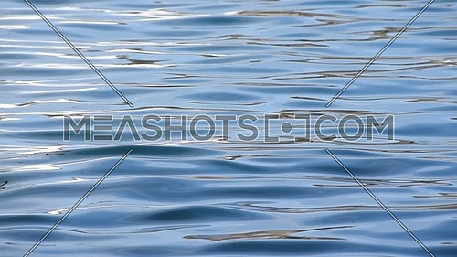 Close up background of blue sea waves and ripples running on water surface