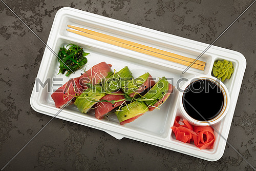 Close up take away set of six raw tuna and avocado sushi rolls in disposable white plastic tray on black table background, elevated top view, directly above
