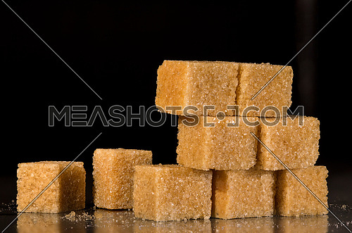 Brown Sugar in its best form Cubes super macro isolated on black