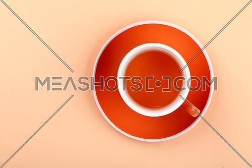 Close up one full red cup of black or fruit tea on saucer over pastel pink paper background, elevated top view, directly above
