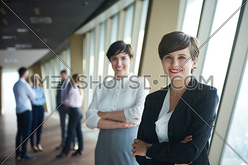 business people group,  females as team leaders standing together  in modern bright office interior