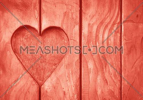 Close up one heart shape, symbol of love and romance, wood carved cut in wooden planks texture background, coral pink painted window shutter