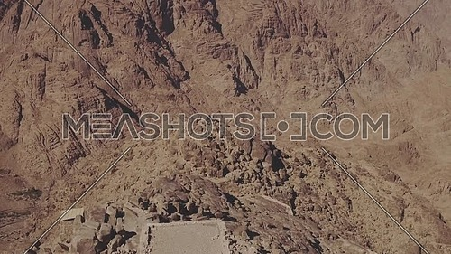 Ariel Shot fly over Moses Mountain showing church and mosque on top the mountain at day.