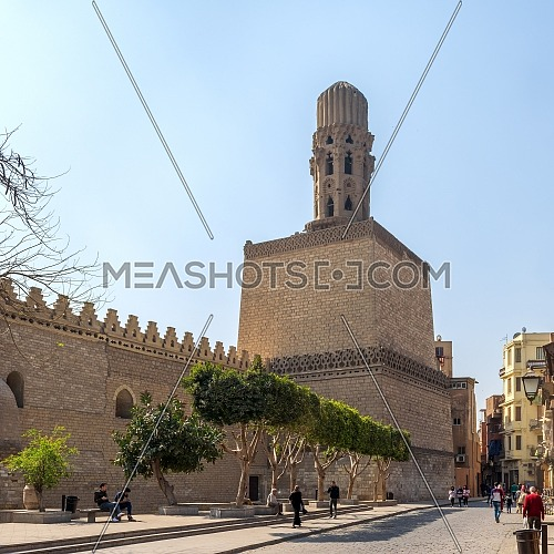 Cairo, Egypt- March 21 2015: Minaret of public historic Al Hakim Mosque known as The Enlightened Mosque, located in Moez Street with walking local residents, Old Cairo