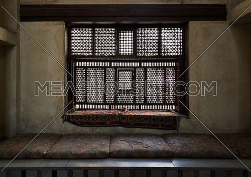 Aged interleaved wooden window (Mashrabiya) and a built-in couch in a room at Al Sehemy house, Cairo, Egypt