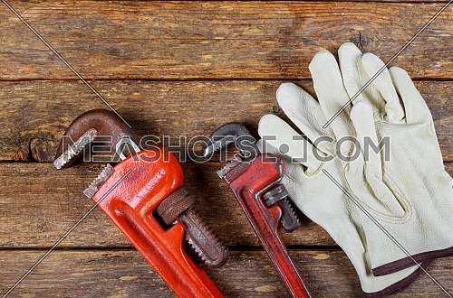 Plumbing wrench leather safety gloves construction concept.