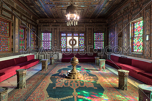 Manial Palace of Prince Mohammed Ali. Syrian Hall with ornate wooden wall and ceiling, windows with colored stained glass and Ottoman Empire logo, old ornate chandelier, red couches, tea tables and ornate carpet