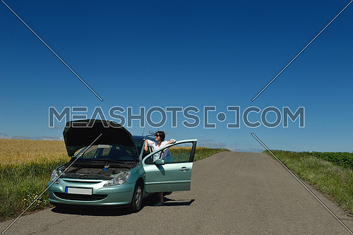 portrait of young beautiful woman with broken car outdoor