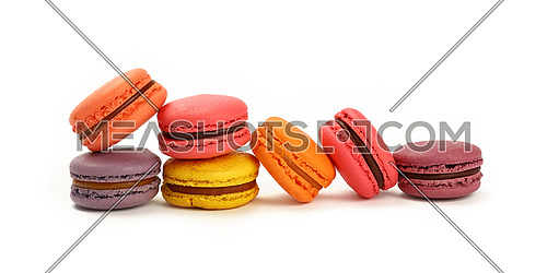 Group of several fresh colorful traditional French macaroon pastry cookies (macarons, macaroni) isolated on white background, close up, low angle view