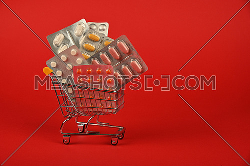 Close up several different blister packs of pills in small shopping cart over red background, concept of online medicine order delivery, low angle view