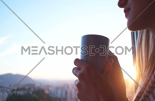 woman drinking coffee or tea by the window during sunset
