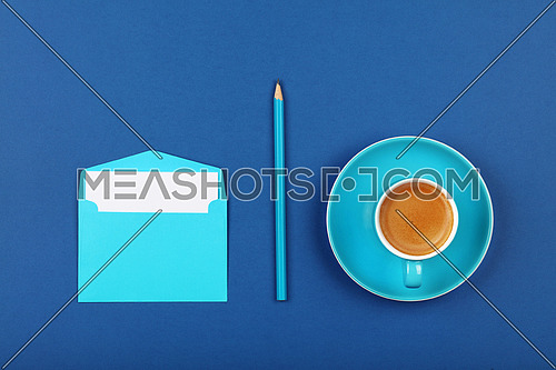 One open blank pastel blue envelope with white paper, espresso coffee cup and wooden pencil over dark indigo blue background, flat lay, directly above