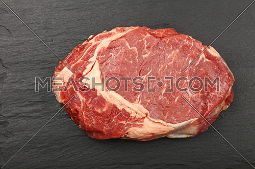 Close up one raw ribeye beef steak on black slate board background, elevated top view, directly above