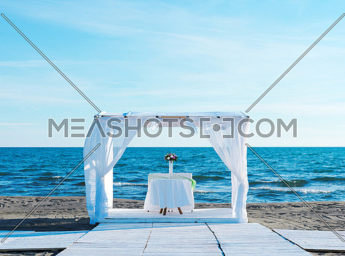 romantic white wedding table set up on tropical beach