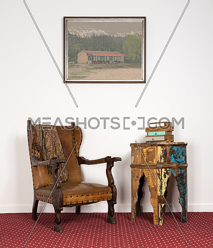 Composition of leather wooden armchair, small drawer unit on vintage round table and framed painting on red carpet and white wall on living room