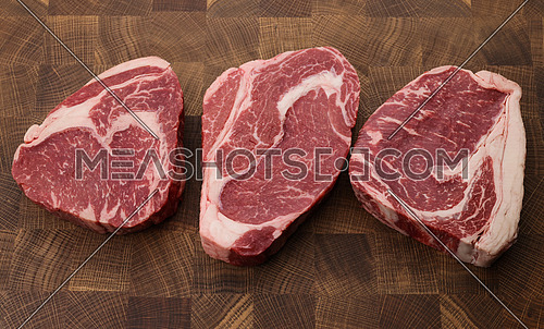 Close up three raw marbled ribeye beef steaks over end grain cutting board of wooden butcher block, high angle view, directly above
