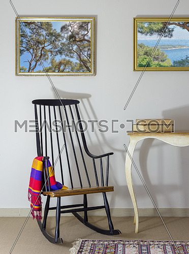 Interior shot of classic rocking chair and two old books on old style vintage table on background of off white wall with two hanged paintings including clipping path for paintings
